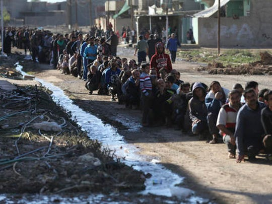 Iraqi citizens sit on the ground in a queue to receive