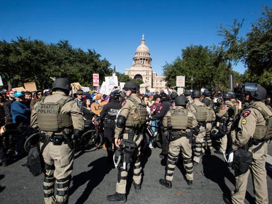 Police in riot gear separate counter-protestors from