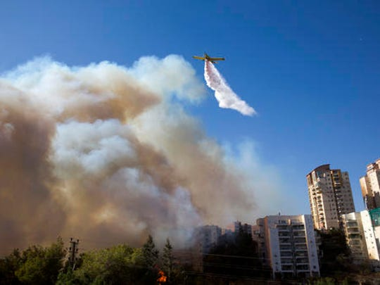 A plane flies over the wildfires in Haifa, Israel, Thursday, Nov. 24, 2016. Israeli police have arrested four Palestinians in connection with one of several large fires that damaged homes and prompted the evacuation of thousands of people in the past few days. Police are investigating the causes, including possible arson. Windy and hot weather have helped fan the flames. The blazes started three days ago near Jerusalem and in the north. Hundreds of homes were damaged. Russia, Italy and other countries are assisting the Israeli firefighters.
