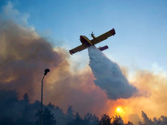 A firefighting plane from Greece fights a wildfire over Haifa, Israel, Thursday, Nov. 24, 2016. A raging wildfire ripped through parts of Israel's third-largest city on Thursday, forcing tens of thousands of people to evacuate their homes and prompting a rare call-up of hundreds of military reservists to join overstretched police and firefighters. Spreading quickly due to dry, windy weather, the fire quickly spread through Haifa's northern neighborhoods. While there were no serious injuries, several dozen people were hospitalized for smoke inhalation.