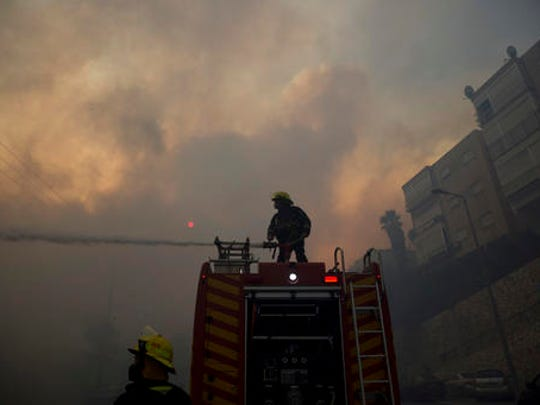 Firefighters fight wildfires in Haifa, Israel, Thursday, Nov. 24, 2016. A raging wildfire ripped through parts of Israel's third-largest city on Thursday, forcing tens of thousands of people to evacuate their homes and prompting a rare call-up of hundreds of military reservists to join overstretched police and firefighters. Spreading quickly due to dry, windy weather, the fire quickly spread through Haifa's northern neighborhoods. While there were no serious injuries, several dozen people were hospitalized for smoke inhalation.