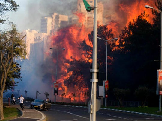 People run as wildfires rages in Haifa, Israel, Thursday, Nov. 24, 2016. A raging wildfire ripped through parts of Israel's third-largest city on Thursday, forcing tens of thousands of people to evacuate their homes and prompting a rare call-up of hundreds of military reservists to join overstretched police and firefighters. Spreading quickly due to dry, windy weather, the fire quickly spread through Haifa's northern neighborhoods. While there were no serious injuries, several dozen people were hospitalized for smoke inhalation.