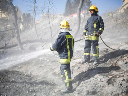 Palestinian firefighters work in Haifa, Israel, Friday, Nov. 25, 2016. Firefighters have reined in a blaze that spread across Israel's third-largest city of Haifa and forced tens of thousands of people to flee their homes.