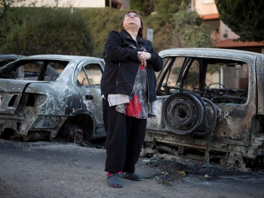 A woman looks at a damaged building next to burned cars following a wildfires in Haifa, Israel, Friday, Nov. 25, 2016. Israeli firefighters on Friday reined in a blaze that had spread across the country's third-largest city of Haifa and forced tens of thousands of people to flee their homes, but continued to battle more than a dozen other fires around the country for the fourth day in a row.