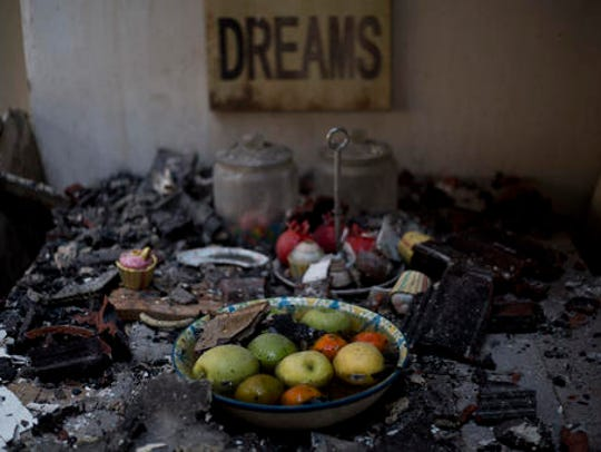 Fruits are inside a bowl on a burned table in a house