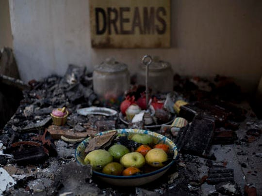 Fruits are inside a bowl on a burned table in a house following a wildfires in Haifa, Israel, Friday, Nov. 25, 2016. Israeli firefighters on Friday reined in a blaze that had spread across the country's third-largest city of Haifa and forced tens of thousands of people to flee their homes, but continued to battle more than a dozen other fires around the country for the fourth day in a row.