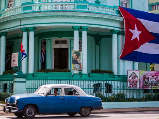 A Cuban flag flies at half-mast, left, and a picture