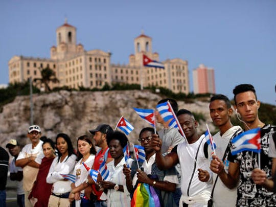 Backdropped by the Hotel Nacional, people hold Cuban