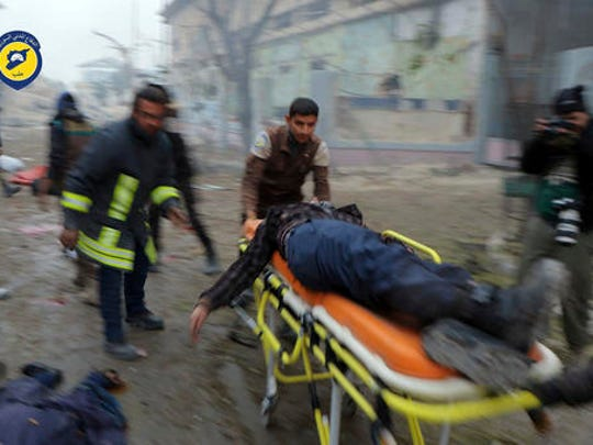This photo provided by the Syrian Civil Defense White Helmets, which has been authenticated based on its contents and other AP reporting, shows Civil Defense workers carrying a victim on a stretcher after artillery fire struck the Jub al-Quba district in Aleppo, Syria, Wednesday, Nov. 30, 2016. Syrian activists say at least 21 people have been killed in an artillery barrage on a housing area for those displaced in rebel-held eastern Aleppo.