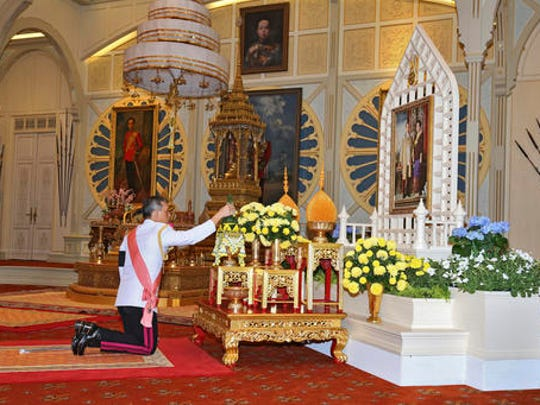 In this photo release by Bureau of the Royal Household, Thailand 's new king Maha Vajiralongkorn Bodindradebayavarangkun pays his respects to a portrait of the late Thai King Bhumibol Adulyadej and Thai Queen Sirikit  at the Dusit Palace Thursday, Dec.1, 2016 in Bangkok, Thailand. Thailand has a new king, with the country's crown prince formally taking the throne to succeed his much-revered late father, who reigned for 70 years.