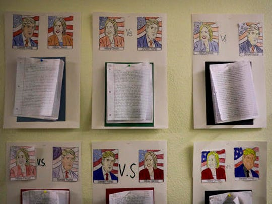 In this Nov. 18, 2016 photo, Muslim students' essays on 2016 presidential candidates, Hillary Clinton and Donald Trump, are pinned to the wall in the hallway at the Islamic Academy of Riverside in Riverside, Calif.  Nationwide, hate crimes against Muslims were up last year and President-elect Donald Trump frequently used heated rhetoric about Muslims on the campaign trail.