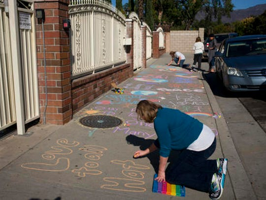In this Nov. 25, 2016 photo, Karen Fagan, joined by her daughters, Kate and Elizabeth Bowman in rear, writes chalk messages on the sidewalk outside the Islamic Center of Claremont in Pomona, Calif., to show their support for Muslim communities. Fagan's ex-husband and her two daughters' father, Harry Bowman, was killed in the Dec. 2, 2015, terror attack at the Inland Regional Center in San Bernardino, Calif.