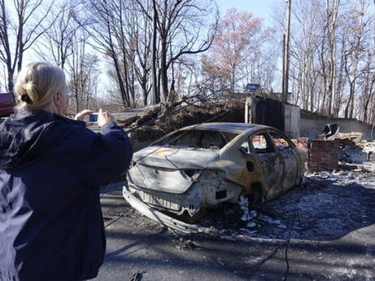Charlotte Moore takes a picture of what remains of her car in the Roaring Fork neighborhood of Gatlinburg, Tenn., Friday, Dec. 2, 2016. Residents on Friday, were getting their first look at what remains of their homes and businesses in Gatlinburg, after a wildfire tore through the resort community on Monday, Nov. 28.