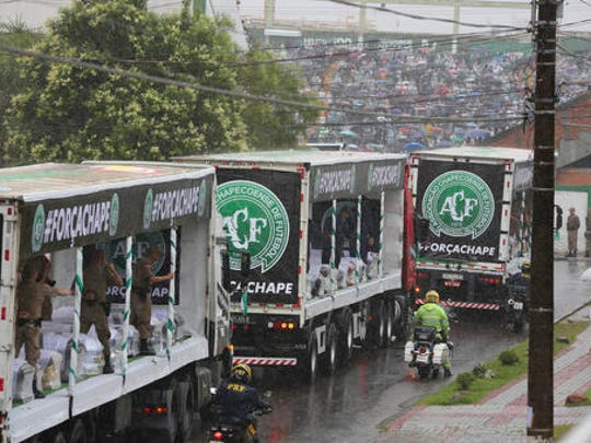 Trucks carrying the coffins with the remains of Chapecoense soccer team members, victims of an air crash in Colombia, drive through the streets of Chapeco, Brazil, Saturday, Dec. 3, 2016.