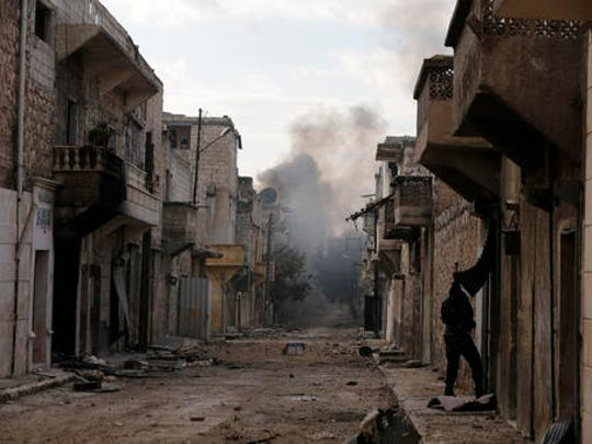 Smoke rises in the east Aleppo neighborhood of Tariq al-Bab after insurgents militants launch a mortar shell on government soldiers, Syria, Saturday, Dec. 3, 2016. Tariq al-Bab was captured by Syrian government forces on Friday.