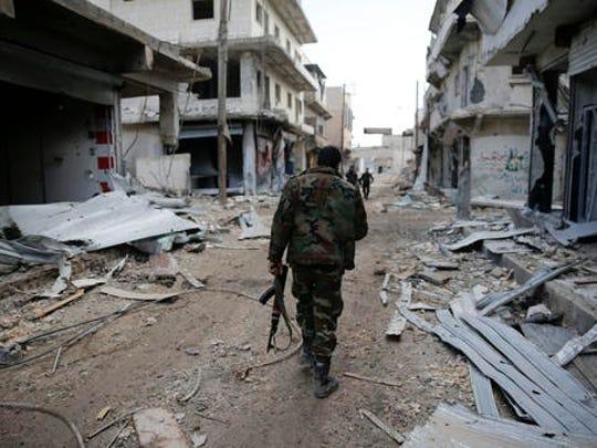 Syrian army soldiers patrol the east Aleppo neighborhood of Tariq al-Bab, Syria, Saturday, Dec. 3, 2016. Tariq al-Bab was captured by Syrian government forces on Friday.