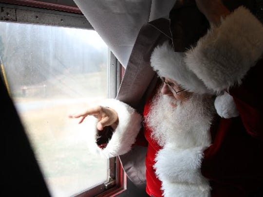 Santa waves to the crowd from inside the caboose of the Santa Express as it approaches its stop in the Cheddar community in December 2008.