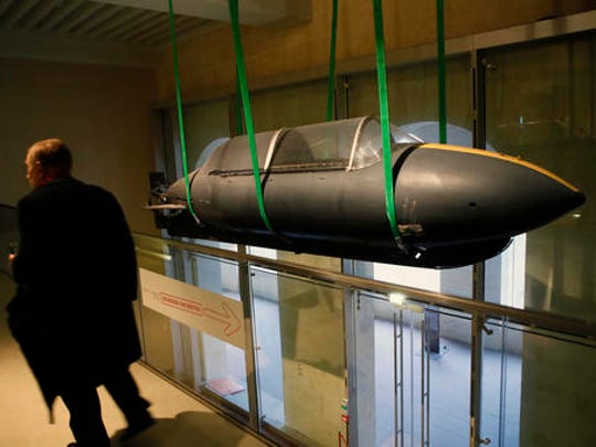 A visitor walks by a 1970 real submarine used by the French secret agents as real-life spy gadgets of secret agents around the world are displayed at the 'Secret Wars' exhibition in Invalides War Museum, in Paris, Monday, Dec. 12, 2016. 'Secret Wars' displays about 400 objects, devices and archives from World War I to the end of the Cold War of French, British, American and German collections, most of which have never been shown before.