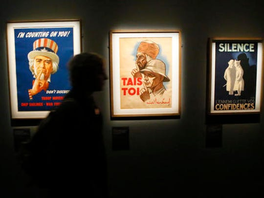 A visitor walks by propaganda warning placards with real-life spy gadgets of secret agents around the world as part of the 'Secret Wars' exhibition at the Invalides Museum, in Paris, Monday, Dec. 12, 2016. 'Secret Wars' displays about 400 objects, devices and archives from World War I to the end of the Cold War of French, British, American and German collections, most of which have never been shown before.
