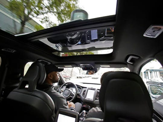 In this photo taken Tuesday, Dec. 13, 2016, Devin Greene sits in the front seat of an Uber driverless car during a test drive in San Francisco. Uber is bringing a small number of self-driving cars to its ride-hailing service in San Francisco - a move likely to both excite the city's tech-savvy population and spark a conflict with California regulators. The Wednesday, Dec. 14, launch in Uber's hometown expands a public pilot program the company started in Pittsburgh in September.