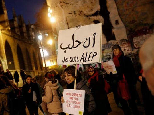 "A woman holds a poster reading ""I'm Aleppo"" during a gathering in a show of support for Aleppo citizens, in Paris, Wednesday, Dec. 14, 2016. A cease-fire designed to allow for the evacuation of civilians and rebels crumbled Wednesday as government bombing resumed."