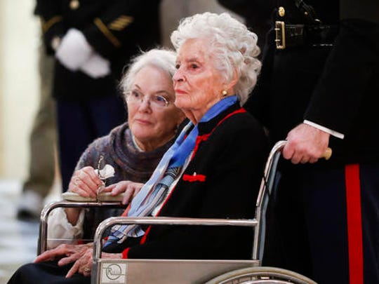 Annie Glenn, center, looks at her husband John Glenn's casket alongside her daughter Carolyn Ann Glenn as he lies in honor, Friday, Dec. 16, 2016, in Columbus, Ohio. Glenn's home state and the nation began saying goodbye to the famed astronaut who died last week at the age of 95.