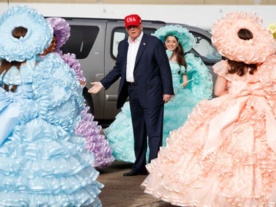President-elect Donald Trump is greeted by the Azalea Trail Maids after arriving at the airport for a rally at Ladd-Peebles Stadium, Saturday, Dec. 17, 2016, in Mobile, Al.