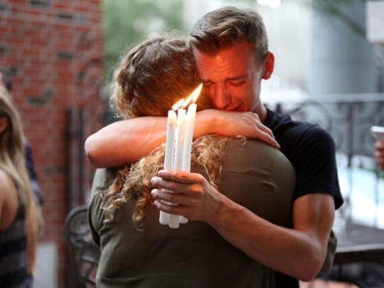 FILE - In this Sunday, June 12, 2016 file photo, Brett Morian hugs an fellow mourner during a candlelight vigil for those killed at the Pulse nightclub in Orlando, Fla. The worst mass shooting in modern U.S. history unfolded on Latin Night at the gay nightclub. The gunman, Omar Mateen, killed 49 people over the course of three hours before dying in a shootout with SWAT team members. During the standoff, he pledged allegiance to the Islamic State.