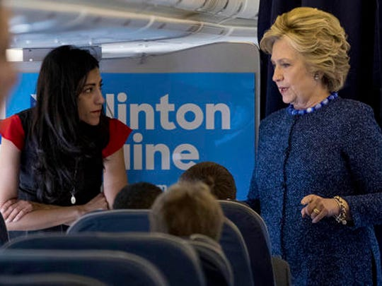 FILE - In this Oct. 28, 2016 file photo, Democratic presidential candidate Hillary Clinton speaks with senior aide Huma Abedin aboard her campaign plane at Westchester County Airport in White Plains. Amid the 2016 presidential campaign, the FBI conducted an investigation into Clinton's use of a private computer server to handle emails she sent and received as secretary of state. FBI Director James Comey criticized Clinton for carelessness but said the bureau would not recommend criminal charges.