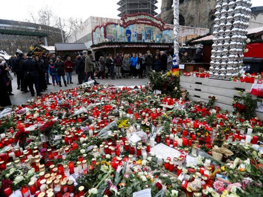 People stand around candles at the reopened Christmas market, three days after a truck ran into the crowd and killed several people, at the Kaiser Wilhelm Memorial Church in Berlin, Thursday, Dec. 22, 2016.