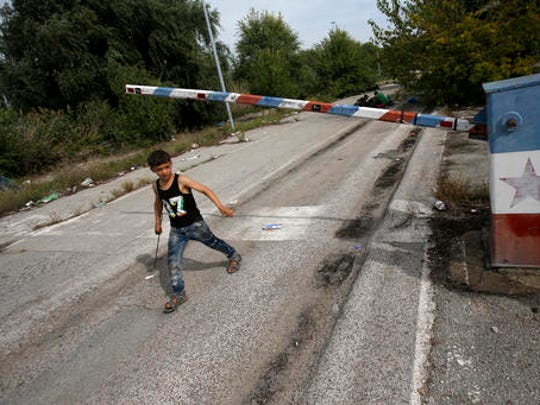 "FILE - In this file photo dated Thursday, Sept. 17, 2015, a migrant child walks at the ""Horgos 2"" border crossing that leads into Hungary, from Horgos, Serbia, with the old Yugoslav communist flag on the abandoned border point. Europe's open borders seem to symbolize liberty and forward thinking, but they increasingly look like the continent's Achilles' heel, with its inability to implement cross border security."