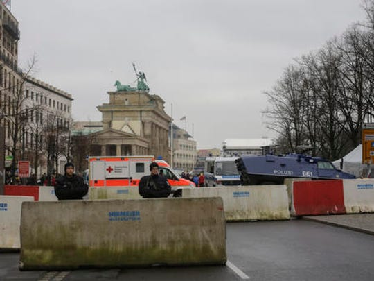 Armed police officers stand behind concrete blocks for protection near the Brandenburg Gate, background, in Berlin, Friday, Dec. 23, 2016, after Anis Amri, the suspect of the terrorist attack on a Christmas market in Berlin was shot in Milan, Italy.