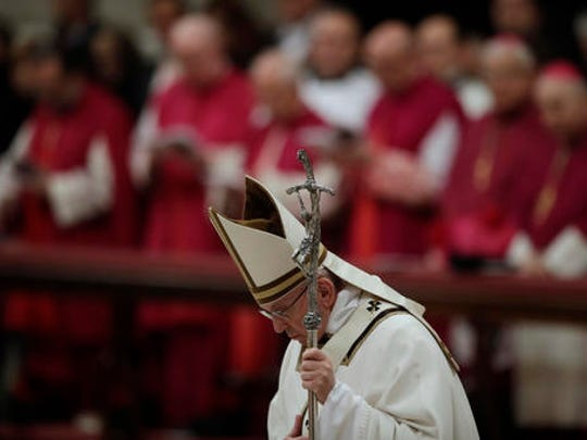 Pope Francis bows in front of the altar as he celebrates the Christmas Eve Mass in St. Peter's Basilica at the Vatican, Saturday, Dec. 24, 2016.