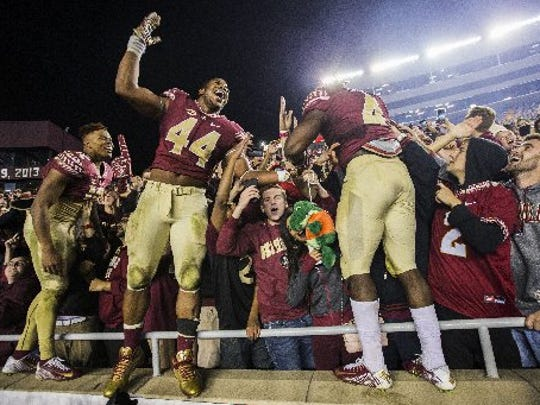 Florida State quarterback Deondre Francois, left, DeMarcus Walker, center, and Dalvin Cook celebrate with fans after Florida State defeated Florida 31-13 in an NCAA college football game in Tallahassee, Fla., Saturday, Nov. 26, 2016.