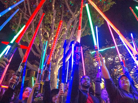 "Fans of actress Carrie Fisher honored her death by pointing their lit ""Star Wars"" light sabers to the sky at 7 p.m. at Downtown Disney, Wednesday night, Dec. 28, 2016, in Anaheim."
