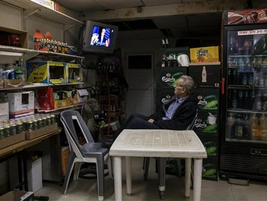 An Israeli grocery store owner watches  the US Secretary