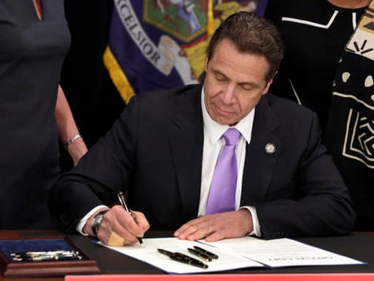 FILE- In this April 4, 2016 file photo, New York Gov. Andrew Cuomo signs a law that will gradually raise New York's minimum wage to $15, at the Javits Convention Center, in New York. New York joins 18 other states by raising its minimum wage in 2017.