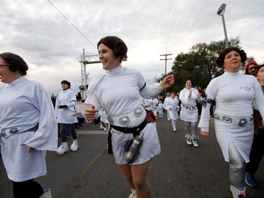 """Members of the Krewe of Chewbacchus, a Mardi Gras Krewe, hold a parade with members dressed as Princess Leia, in honor of actress Carrie Fisher, who played Leia in the """"Star Wars"""" movie series, in New Orleans, Friday, Dec. 30, 2016. Fisher died on Dec. 27, 2016, at the age of 60."""