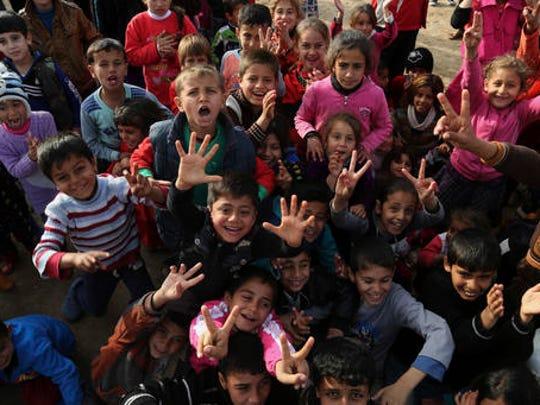 Iraqi internally displaced children cheering during