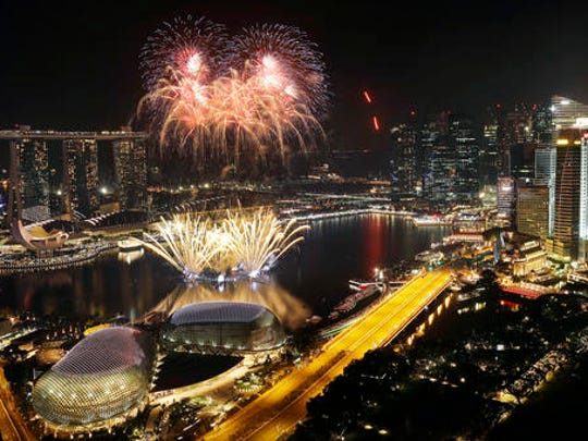 Fireworks explode above Singapore's financial district at the stroke of midnight to mark the New Year's celebrations on Sunday, Jan. 1, 2017, in Singapore.