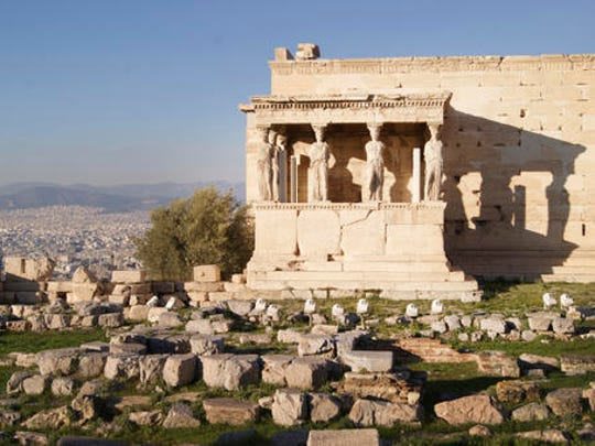 In this Dec. 11, 2016 photo, the Erechtheionin, an ancient Greek temple on the north side of the Acropolis of Athens, is seen against a backdrop of Athens. For travelers with more than beaches on their minds, there's plenty of upside to a brief winter visit to Athens that avoids the crowds and heat of summer.