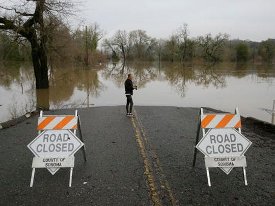 Michelle Wolfe, who had to evacuate her nearby mobile home, looks out toward flooded vineyards in the Russian River Valley, Monday, Jan. 9, 2017, in Forestville, Calif. A massive storm system stretching from California into Nevada lifted rivers climbing out of their banks, flooded vineyards and forced people to evacuate after warnings that hillsides parched by wildfires could give way to mudslides.