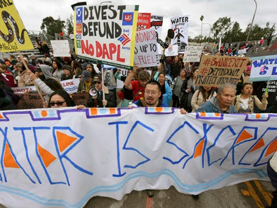 File - In this Jan. 2, 2017, file photo, protesters rally against the Dakota Access Pipeline behind the 128th Rose Parade in Pasadena, Calif. The front lines of the battle against the $3.8 billion Dakota Access pipeline are shifting away from the dwindling encampment in North Dakota.