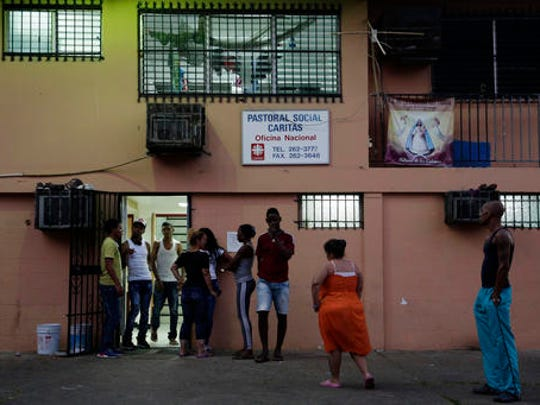 """Cuban migrants, many who are traveling to the U.S., stand outside a shelter in Panama City, Thursday, Jan. 12, 2017. President Barack Obama announced Thursday he is ending a longstanding immigration policy that allows any Cuban who makes it to U.S. soil to stay and become a legal resident. The repeal of the """"wet foot, dry foot"""" policy is effective immediately."""