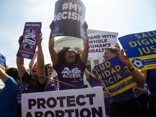 FILE - June 27, 2016 file photo pro-abortion rights activists celebrate during a rally at the Supreme Court in Washington. The tens of thousands of women flocking to Washington for a march on the day after Donald Trump's inauguration come packing a multitude of agendas, but are united in their loathing for Trump.