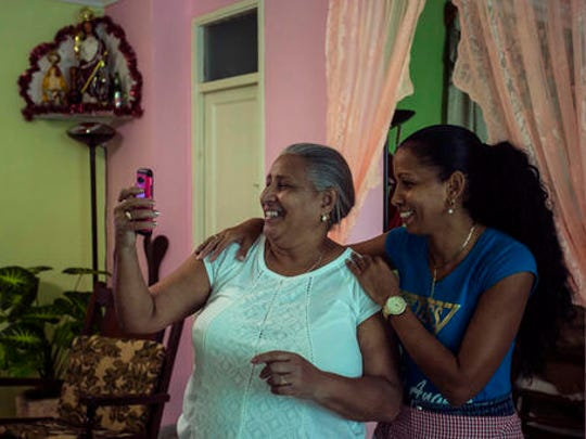 In this Jan. 6, 2017 photo Yolanda Mollinedo looks at her granddaughter Alejandra in Virginia, United States, on her smartphone using a video chat application beside her niece Yulisleidi with the new experimental internet in the living room of her home in Havana, Cuba. The home internet test program selected some 2,000 residents of Old Havana to receive free connections for two months before a planned expansion and the start of billing for the service.