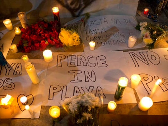 "Candles sit atop banners proclaiming in Spanish ""Peace in Playa,"" ""No more pistols,"" and ""Enough already of so much corruption and impunity,"" outside the Blue Parrot club, where several people were killed in early morning gunfire, in Playa del Carmen, Mexico, Monday, Jan. 16, 2017. Deadly gunfire broke out in the crowded beachfront nightclub throbbing with electronic music before dawn on Monday, setting off a bloody stampede by screaming concertgoers at an international festival in this Caribbean resort."