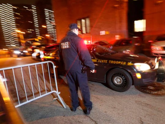 """An official looks on as a New York State Police vehicle, part of a motorcade carrying Mexican drug kingpin Joaquin """"El Chapo"""" Guzman, arrives at the Metropolitan Correctional Center in New York, Thursday, Jan. 19, 2017. The infamous drug kingpin who twice escaped from maximum-security prisons in Mexico was extradited at the request of the U.S. to face drug trafficking and other charges, and landed in New York late Thursday, a federal law enforcement official said."""