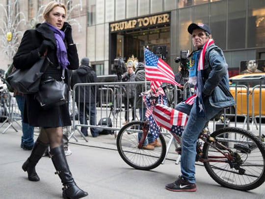 Trump supporter Carlos Aciar, who is originally from Argentina and now lives in Manhattan decorated his bike with American flags to celebrate outside Trump Tower , Friday, Jan. 20, 2017, in New York.