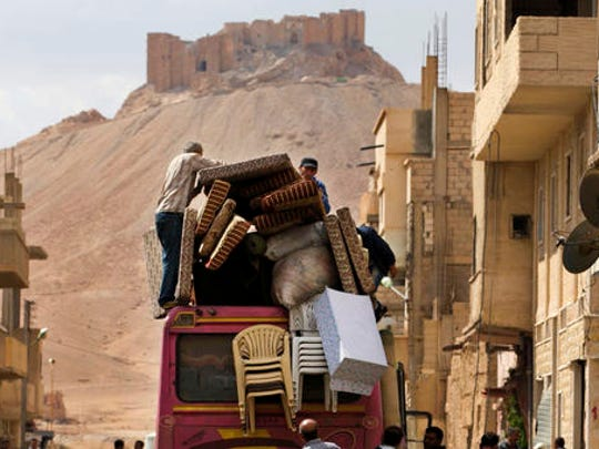 FILE -In this file picture taken Thursday, April 14, 2016, the Palmyra citadel is seen in the background as Syrian families load their belongings onto a bus in the town of Palmyra in the central Homs province, Syria.   Islamic State group militants destroyed a landmark ancient Roman monument and parts of the theater in Syria's historic town of Palmyra, the government and opposition monitoring groups said Friday, Jan. 20, 2017.
